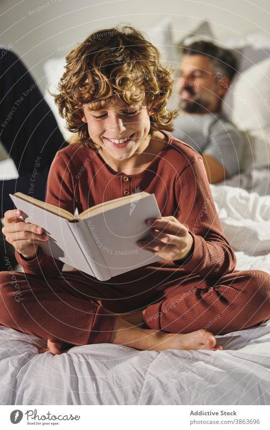 Nettes Kind liest Buch im Zimmer lesen Schlafzimmer clever unterhalten Vater Sohn Bett interessant heimwärts Etage Freude Literatur sitzen Komfort Zusammensein