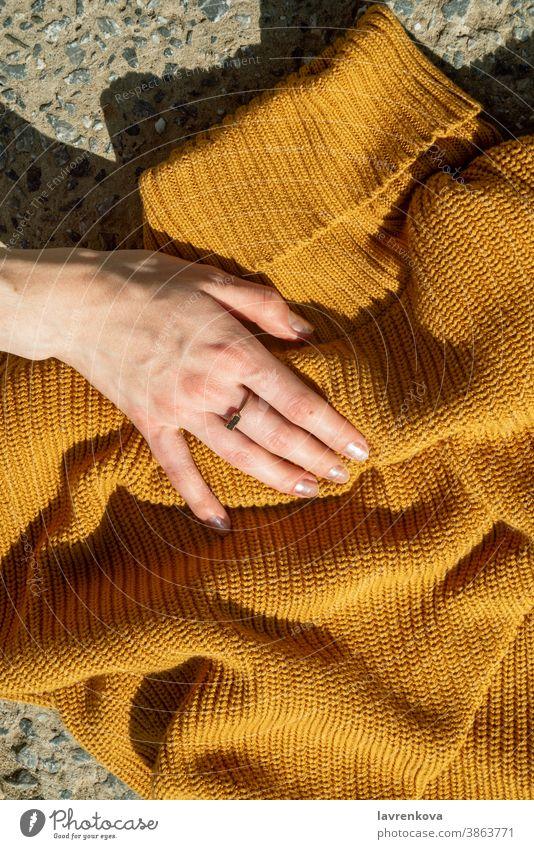 Draufsicht auf Frauenhände, die einen senfgelben Strickpulli auf steinernem Hintergrund berühren Mädchen gestrickt Pullover Hand ohne Gesicht gesichtslos