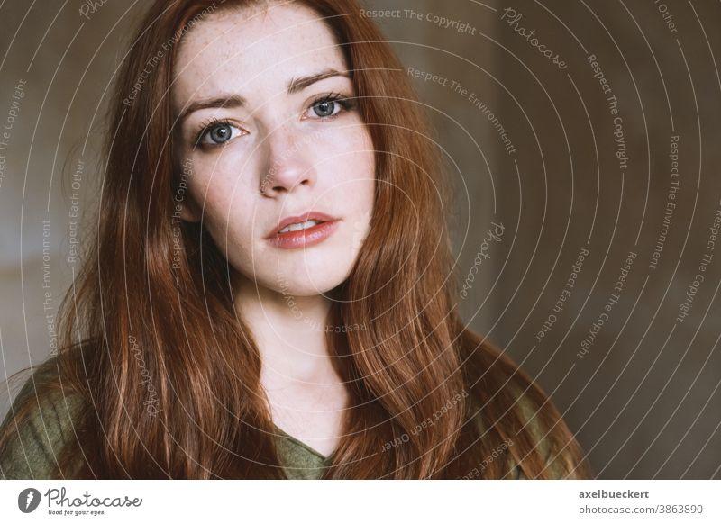 junge Frau in leerem Raum mit natürlichem Licht echte Menschen Porträt Junge Frau verträumt rothaarig Erwachsene langhaarig Sommersprossen Blick in die Kamera