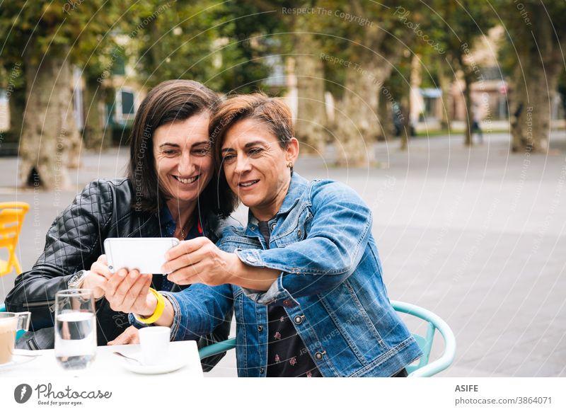 Lesbisches Paar mittleren Alters, das ein Selfie nimmt lesbisch lgbtq schwul mittleres Alter 40 50 Smartphone Selbstportrait Handy Lächeln Homosexualität Frauen