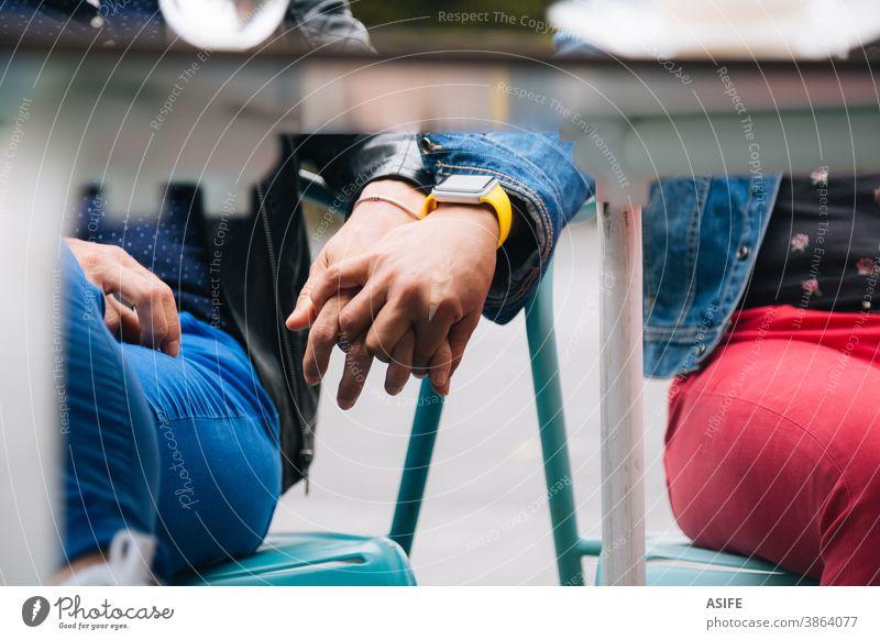 Lesbisches Paar hält Hände unter dem Tisch lesbisch lgbtq schwul mittleres Alter 40 50 Beteiligung Händchenhalten Mittelteil versteckend Homosexualität Frauen