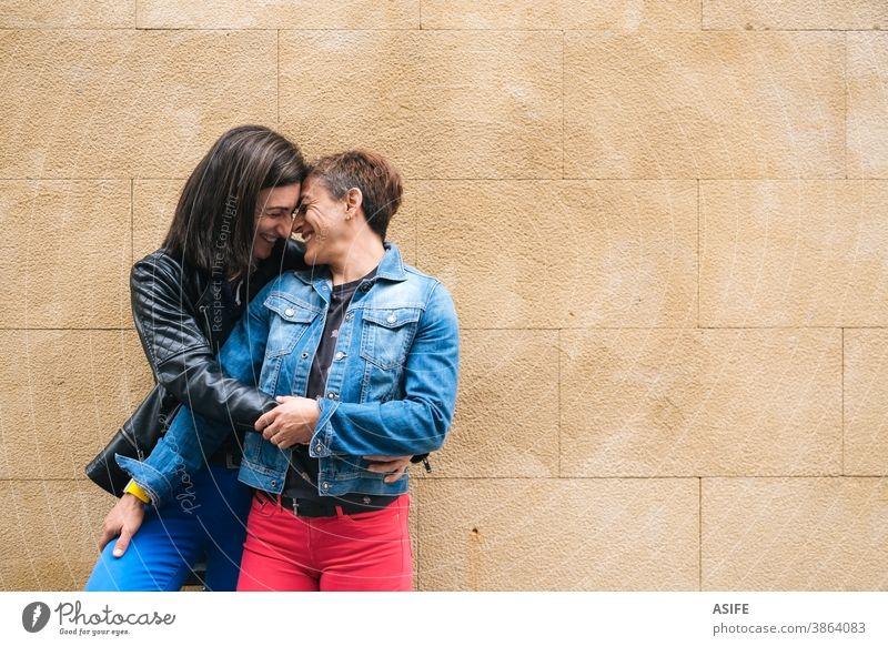 Glückliches lesbisches Paar mittleren Alters umarmt sich im Freien lgbtq schwul mittleres Alter 40 50 umarmend Beteiligung Umarmen Lachen Lächeln Nase