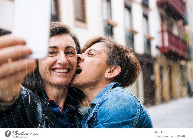 Glückliches lesbisches Paar mittleren Alters mit lustigem Egoismus lgbtq schwul mittleres Alter 40 50 Lachen Selfie Smartphone Selbstportrait Lächeln Umarmen