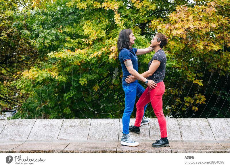 Lesbisches Paar mittleren Alters genießt gemeinsam im Park lesbisch lgbtq schwul mittleres Alter 40 50 umarmend Beteiligung Umarmen Lächeln Homosexualität
