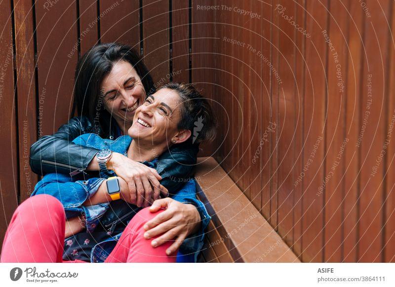 Glückliche Momente in einem lesbischen Paar mittleren Alters lgbtq schwul mittleres Alter 40 50 umarmend Beteiligung Umarmen Lachen Lächeln Homosexualität
