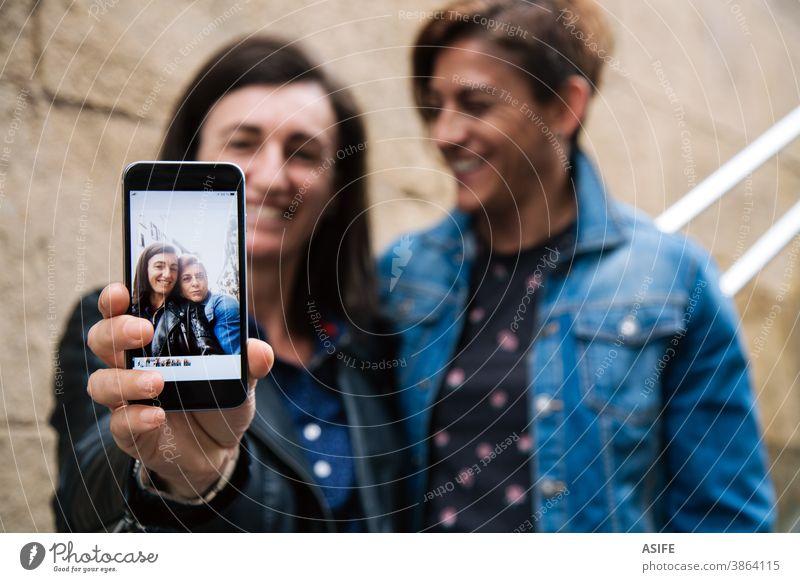 Glückliches lesbisches Pärchen mittleren Alters, das ein Selfie im Smartphone zeigt Paar lgbtq schwul mittleres Alter 40 50 Lachen Selbstportrait Lächeln