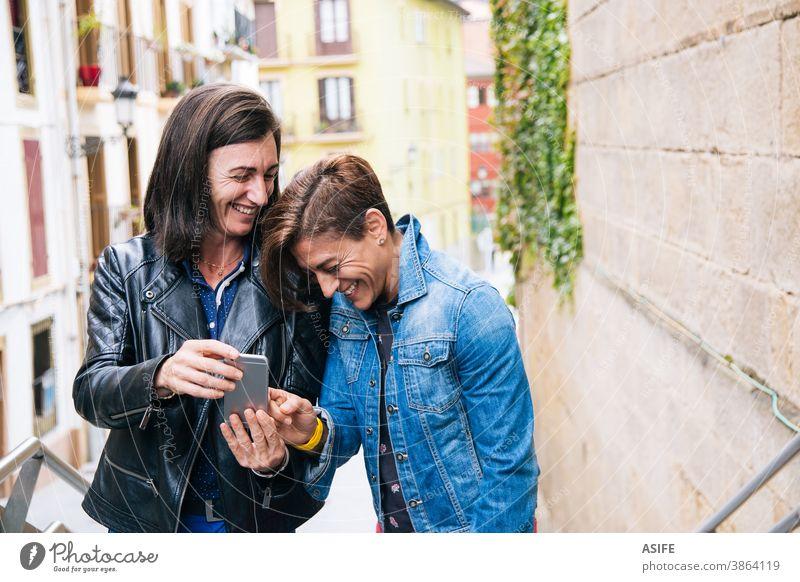 Lustiges lesbisches Paar mittleren Alters, das über etwas im Mobiltelefon lacht lgbtq schwul mittleres Alter 40 50 Lachen Selfie Smartphone Selbstportrait