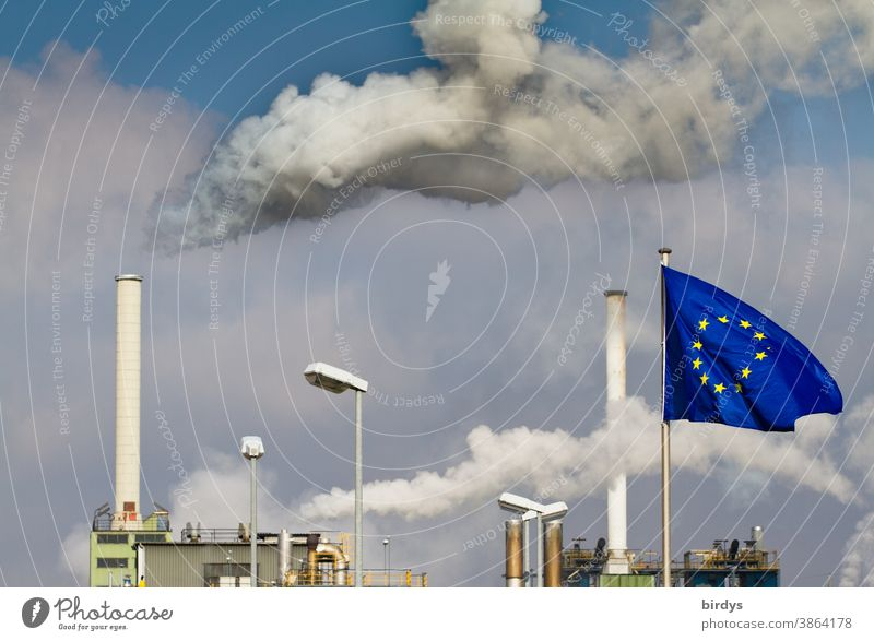 Rauchende Industrieschornsteine . Fabrik mit Europafahne davor .Europäische Union CO2-Ausstoß EU Industrieanlage Schornstein Luftverschmutzung Klimawandel