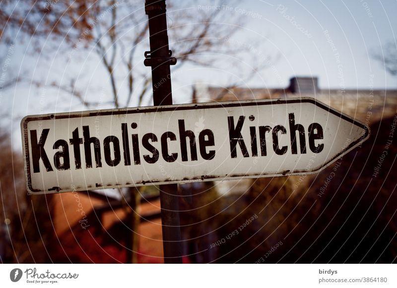 """Richtungsweisendes Straßenschild mit der Aufschrift """" Katholische Kirche """". Katholische Kirche katholische Kirche Katholizismus Zölibat Mißbrauch düster Schrift"""
