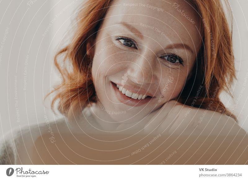 Nahaufnahme einer positiv gestimmten rothaarigen Frau mit sommersprossiger Haut und zahnartigem Lächeln, konzentriert am Bildschirm eines Laptop-Computers, zufrieden mit dem Online-Geschäft, prüft eingegangene Nachricht, hat einen Fernjob