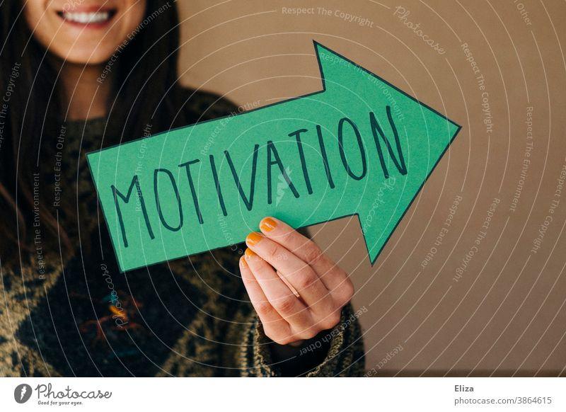Eine Frau hält einen grünen Pfeil mit der Aufschrift Motivation motivieren Lob Anerkennung Beruf Orientierung Zukunft Karriere Erfolg Ziel Richtung ehrgeizig