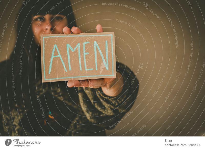 Junge Frau hält ein Schild mit der Aufschrift Amen Kirche Herz Gebet beten Religion & Glaube Christentum Judentum betend Liebe glauben heilig Gottesdienst