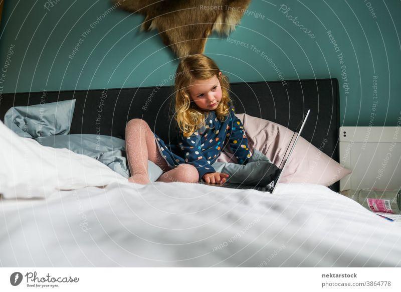 Kleines kaukasisches Mädchen benutzt Laptop im Bett Kind Kaukasier Computer blond 5 Jahre alt Totale reales Leben echte Person Lifestyle häusliches Leben Frau