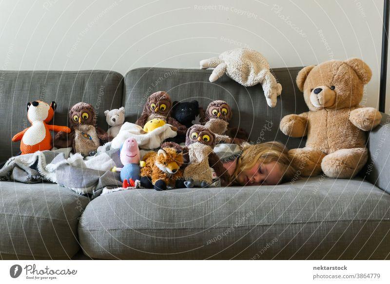 Kollektion gefüllter Spielzeuge auf Sofa mit schlafendem Kind Mädchen Kaukasier Plüschtier Teddybär 1 Mensch Tag Mittagsschlaf Rauen Liege Sammlung obenauf