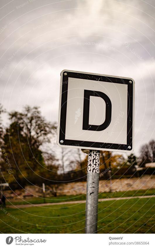 Schild mit Buchstabe D Buchstaben Schilder & Markierungen Elbufer Signal Hinweisschild Wort Zeichen Außenaufnahme Typographie Kommunikation Schriftzeichen