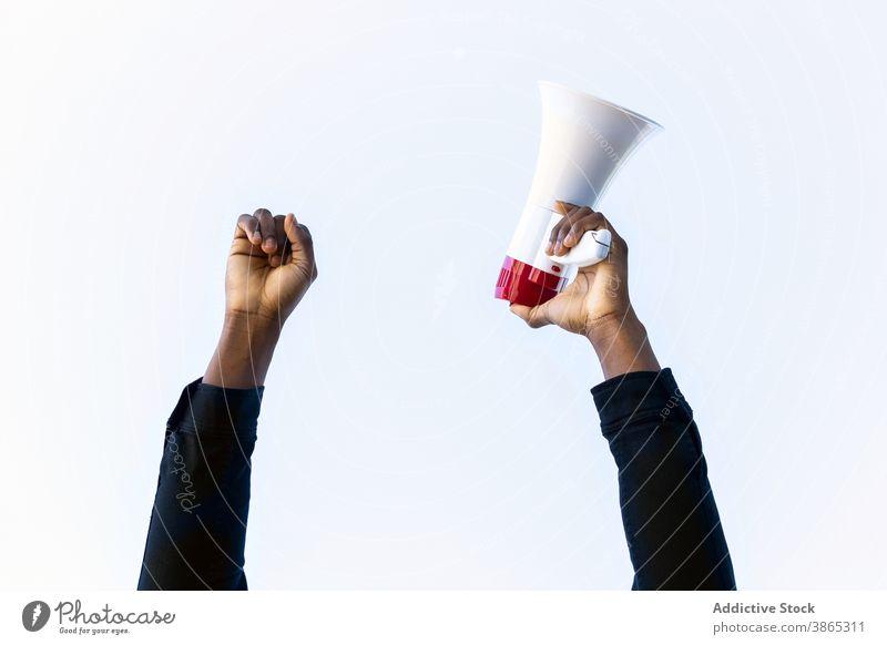 Crop schwarzer Mann mit Lautsprecher in den Händen Megaphon Hupe mit der Faust nach oben erreichen ankündigen Triumph Nachrichten gestikulieren männlich