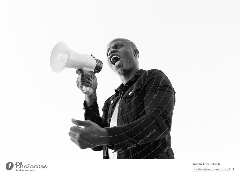 Aufgeregter schwarzer Mann mit Megaphon auf weißem Hintergrund Lautsprecher Schrei Hupe ankündigen verrückt aufgeregt männlich ethnisch Afroamerikaner