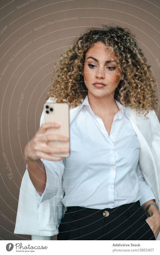 Charmante Frau nimmt Selfie auf Smartphone Lächeln Glück Selbstportrait Gesicht machen Lippe Atelier charmant Telefon Stil Zeitgenosse trendy Apparatur Gerät
