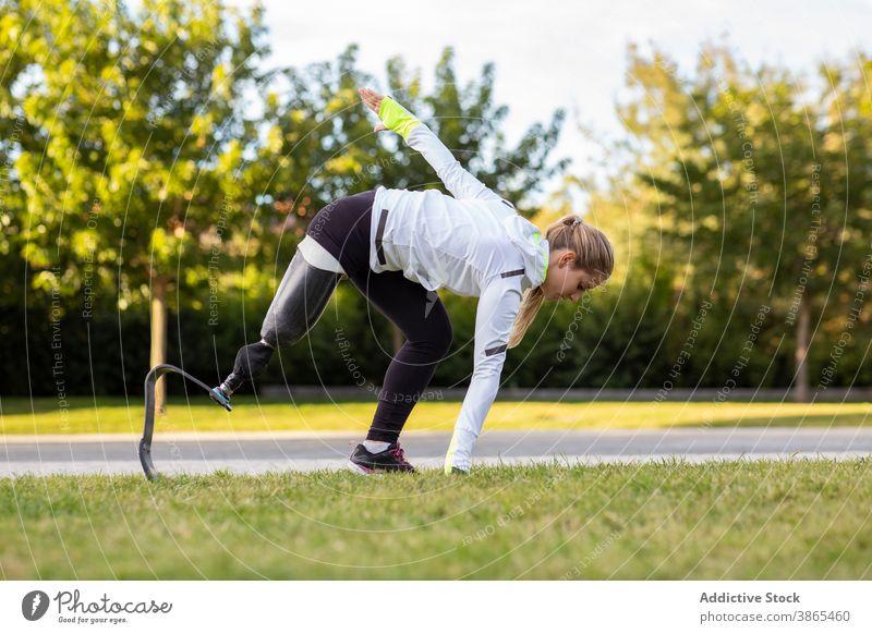 Sportliche Frau mit Beinprothese beim Training im Park explosiv Start Läufer paralympisch Prothesen laufen Sportlerin künstliches Glied Übung Bionik bereit