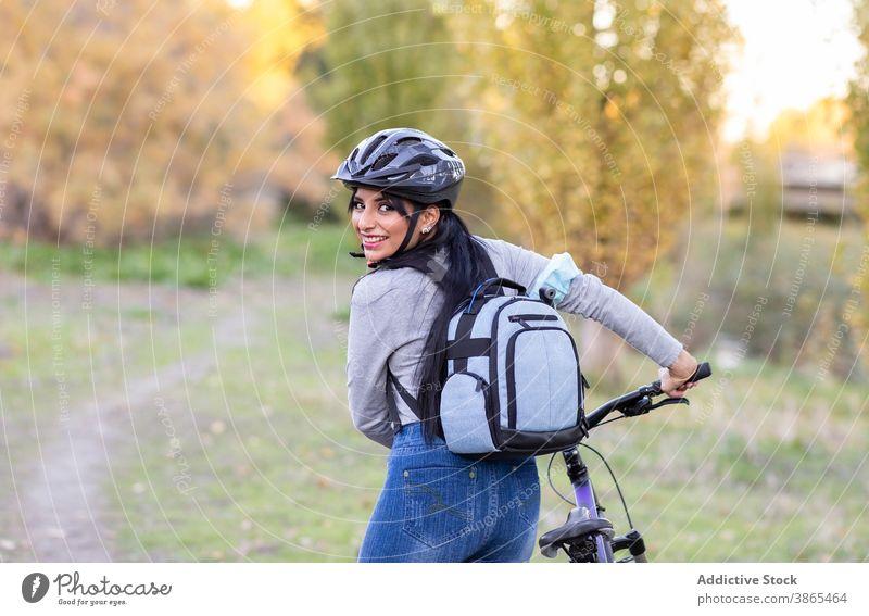 Positive Frau mit Fahrrad in herbstlicher Landschaft Herbst Wald aktiv Glück Natur Mitfahrgelegenheit Rucksack Schutzhelm heiter Lächeln Nachlauf Weg Aktivität