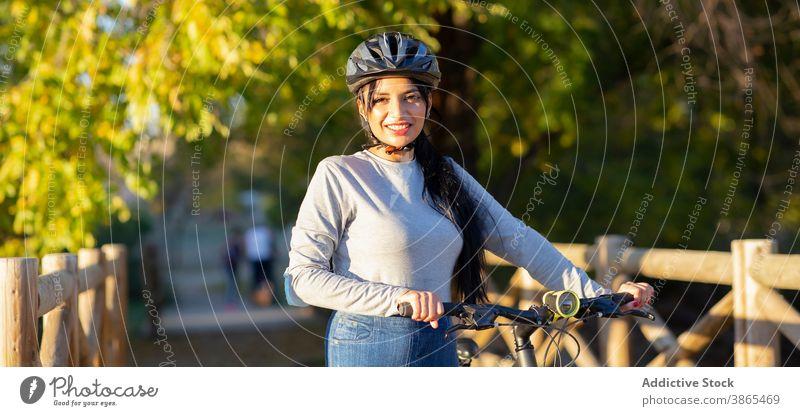 Glückliche Frau fährt Fahrrad im Herbst Wald Mitfahrgelegenheit aktiv Landschaft Natur heiter Lächeln Nachlauf Weg Aktivität Radfahrer Reise erkunden jung