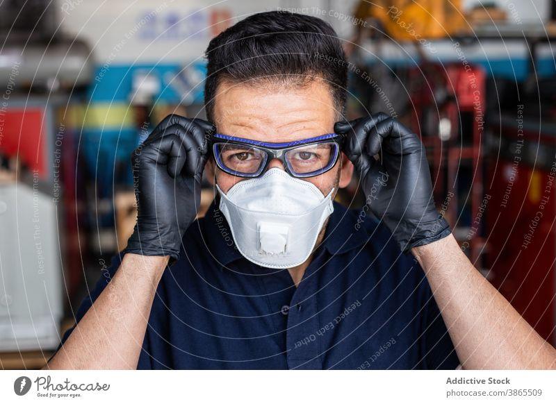 Männlicher Techniker setzt Schutzbrille auf Mann Mechaniker angezogen Garage Atemschutzgerät Handschuh vorbereiten behüten Arbeiter männlich Latex Erwachsener
