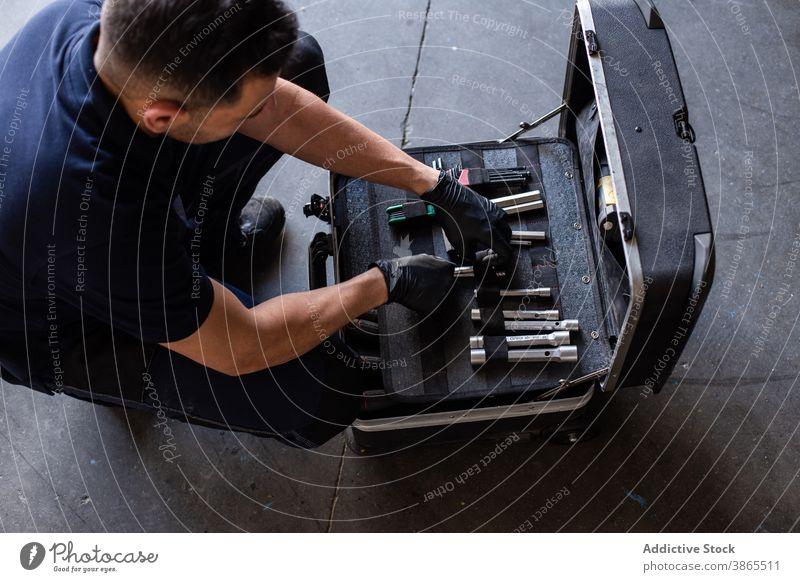 Mechaniker wählt Bits aus der Box aus Mann Kasten Meissel wählen Garage Arbeit Schraubendreher Werkzeug professionell männlich Techniker Job Werkstatt Beruf