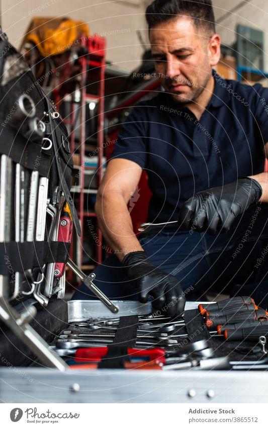 Bild eines Mechanikers, der Bits aus einer Box auswählt Mann Kasten Meissel wählen Garage Arbeit Schraubendreher Werkzeug professionell männlich Techniker Job