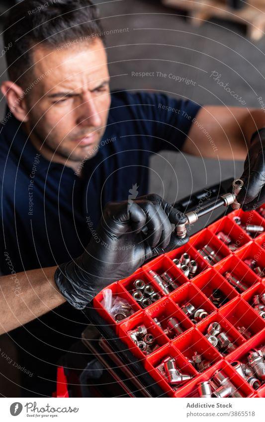 Männlicher Techniker prüft Werkzeug in der Werkstatt Mann Mechaniker untersuchen Kasten Garage Arbeit Handschuh modern professionell männlich Erwachsener