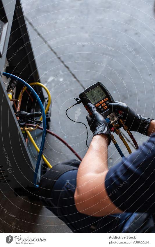 Mann beim Prüfen der Spannung einer defekten Maschine Mechaniker prüfen Tester modern gebrochen Werkstatt Arbeit Gerät männlich Schutzbrille Handschuh manuell