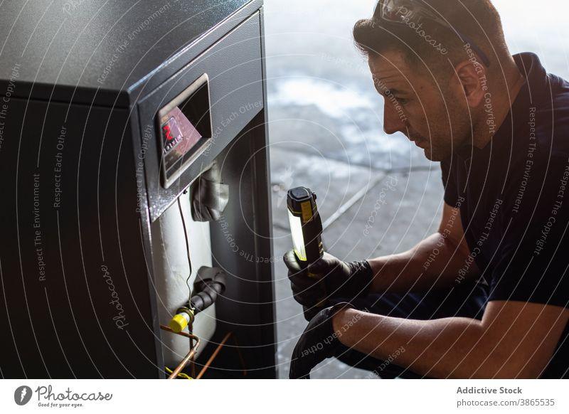 Mechaniker mit Taschenlampe, der den Mechanismus in der Werkstatt untersucht untersuchen prüfen Reparatur Arbeit Maschine Werkzeug Mann Licht professionell