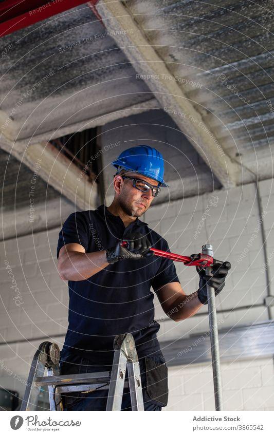 Arbeiter bei der Installation von Rohren mit Schraubenschlüssel in der Werkstatt Röhren Klempner installieren Handwerker Werkzeug Mann professionell heiter