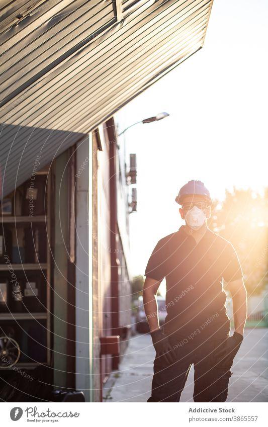 Professionelle Mechaniker stehen in der Nähe Werkstatt Gebäude Arbeiter Atemschutzgerät Mundschutz behüten professionell Mann Beruf männlich Dienst Lifestyle