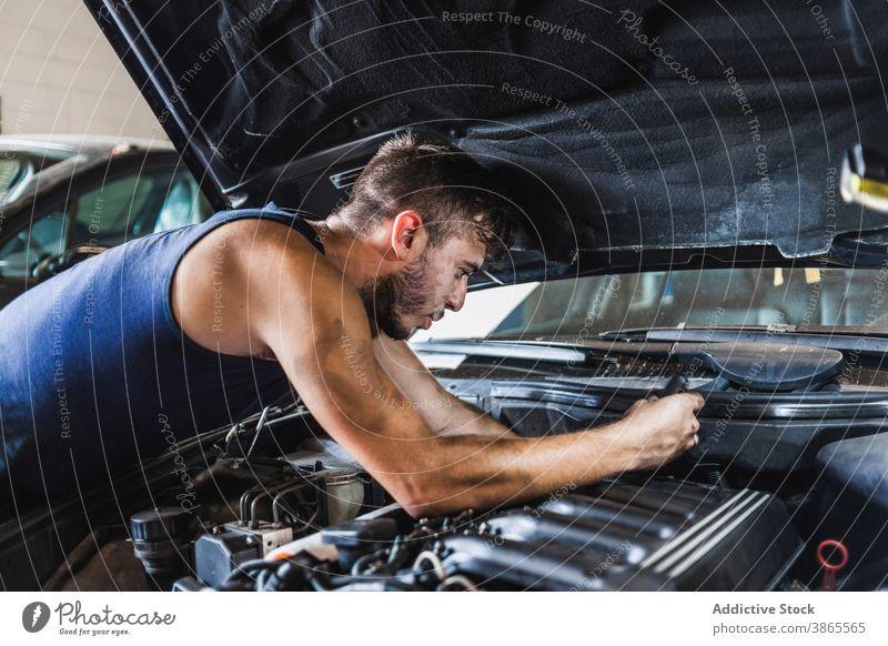 Männlicher Mechaniker schraubt Motor eines Autos ab Mann schrauben PKW Garage Arbeit dreckig Flugzeugwartung Reparatur männlich fixieren Fahrzeug Verkehr Beruf