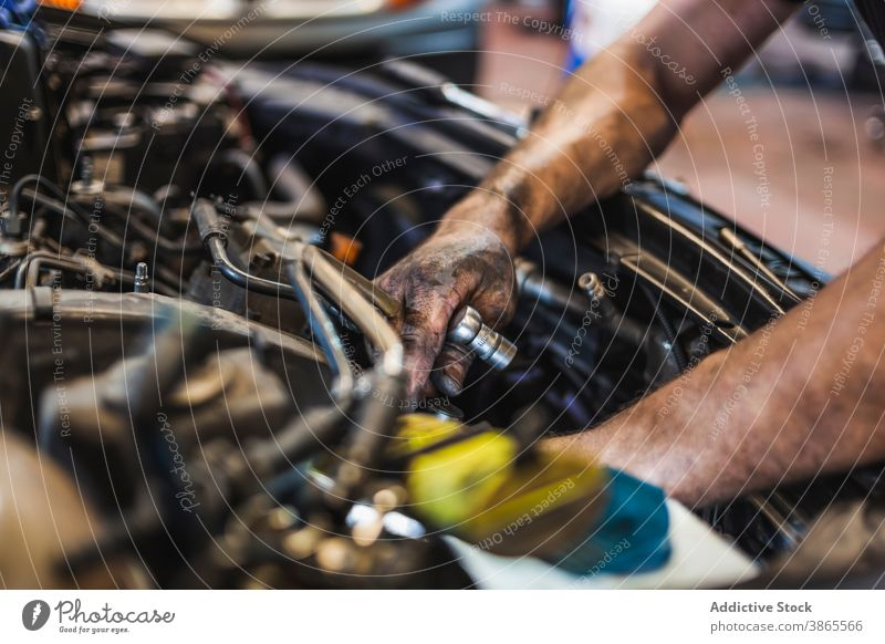 Crop-Techniker mit Taschenlampe bei der Untersuchung eines Automotors Mann Mechaniker prüfen Motor PKW Garage leuchten Arbeit Reparatur männlich Fahrzeug