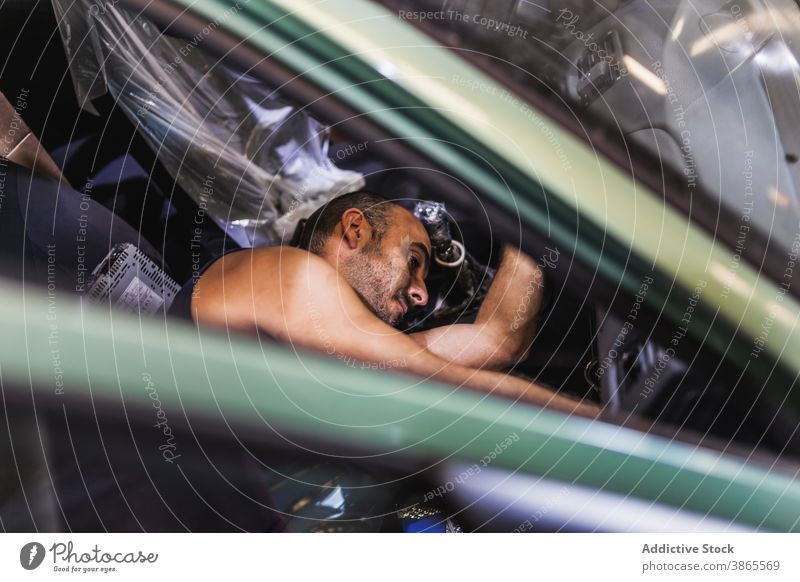 Männlicher Techniker, der das Armaturenbrett eines Autos überprüft Mann prüfen PKW Garage Arbeit Sitz modern Dienst männlich Erwachsener Lügen Passagier