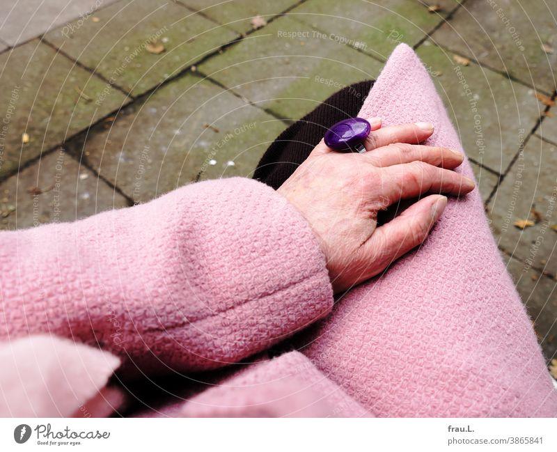 Alte Frauenhand mit rosa Mantel, rosa Schal und violettem Ring sowie kleiner Katerkratzwunde Hand Mensch Strickrock Mode Fingerring Modeschmuck Fußweg sitzen