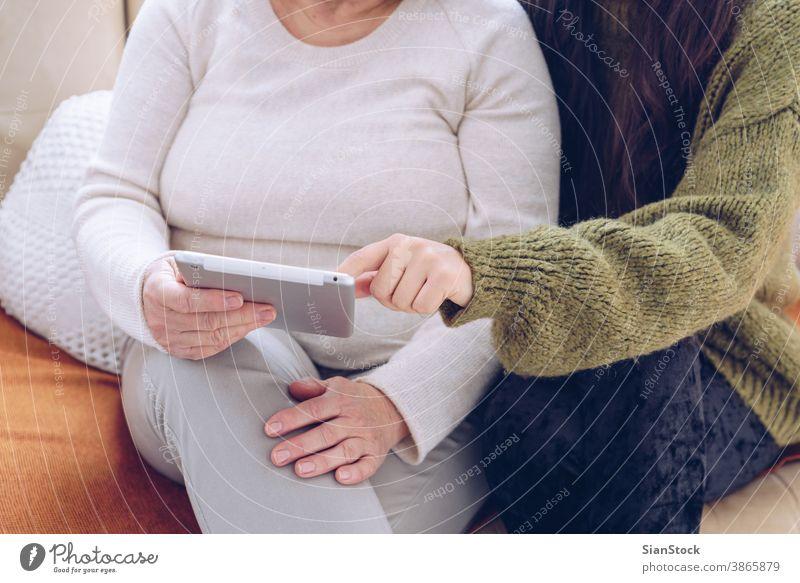 Tochter hilft ihrer älteren Mutter mit der Tablette Senior online jung Frau Hände Erwachsener Person Arzt Frauen verwenden digital zeigen weiß