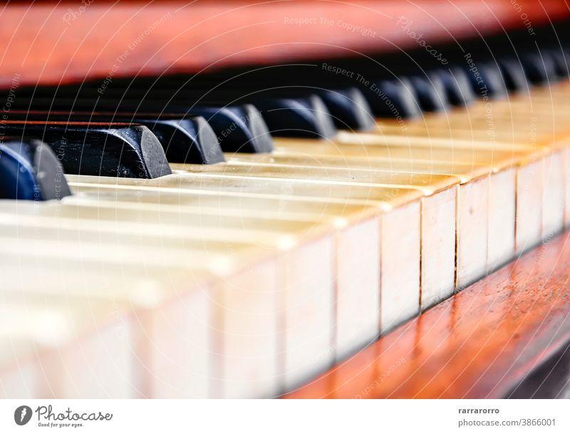 Nahaufnahme der Tasten eines alten abgenutzten Klaviers. Keyboard Instrument Musical Detailaufnahme Schwarzer Schlüssel Holz Elfenbein Antiquität