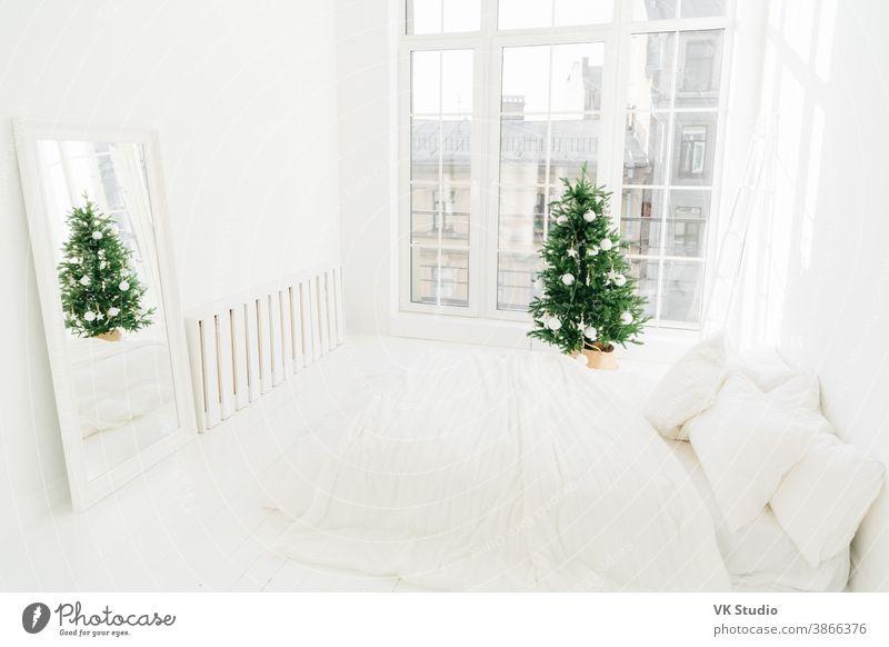 Komfort-, Haus- und Heiligabend-Konzept. Schlafzimmer mit weißem Softbett, Spiegel, großem Fenster für Lichteinfall, dekoriertem Neujahrsbaum und Leiter. Feiertags-Dekoration.
