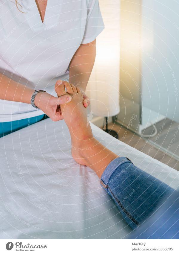 Therapeutin gibt eine Fußmassage während einer Physiotherapie-Sitzung in einer modernen Klinik Physiotherapeutin Rehabilitation Massage Frau berühren Medizin