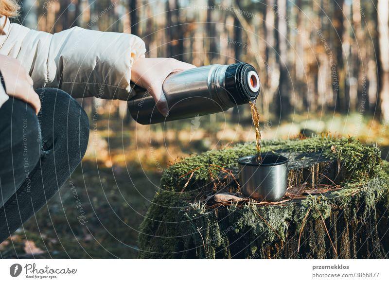 Frauen, die während der Herbstreise Pause machen und am kalten Herbsttag ein heißes Getränk aus der Thermoskanne gießen. Aktive Frauen, die in einem Wald wandern und aktiv Zeit verbringen