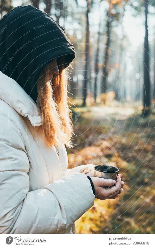Frau mit Kapuze, die während einer Herbstreise eine Tasse mit heißem Getränk aus der Thermoskanne an einem kalten Herbsttag in der Hand hält. Aktives Mädchen wandert in einem Wald und verbringt aktiv Zeit