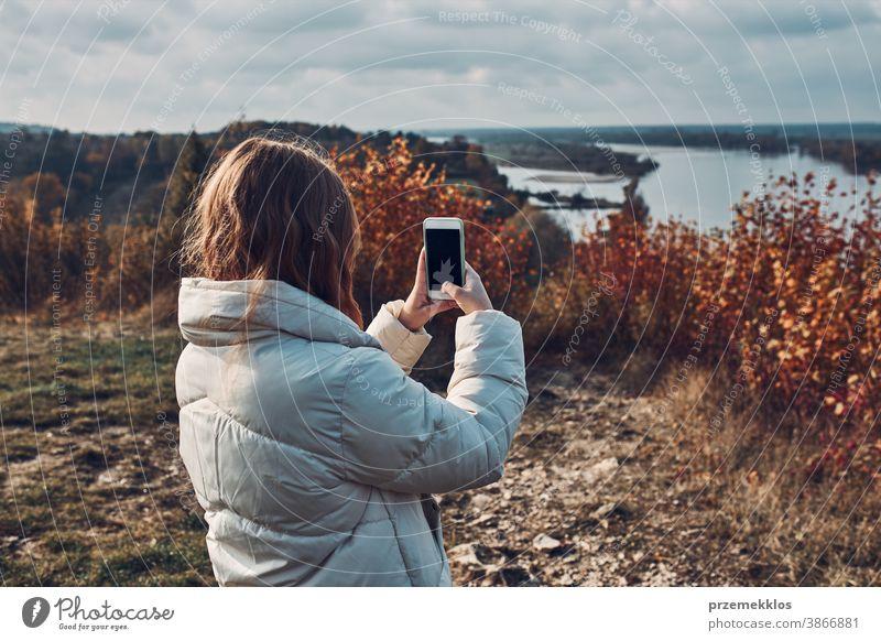 Rückansicht einer jungen Frau, die während einer Reise an einem sonnigen Herbsttag mit einem Smartphone Fotos von der Landschaft macht Junge Frau nehmen unter