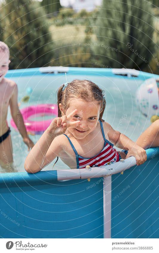 Glückliches Mädchen macht V-Zeichen-Geste und spielt in einem Pool und genießt das Plantschen und den Spaß mit den Geschwistern an einem sonnigen Sommertag