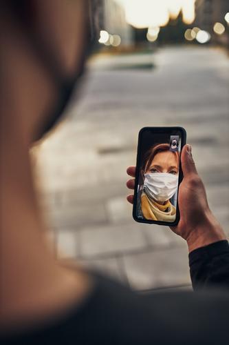 Junger Mann, der eine Videokonferenz mit seiner Mutter führt, die abends auf der Straße steht und die Gesichtsmaske trägt, um eine Virusinfektion zu vermeiden und die Ausbreitung der Krankheit bei Auftreten des Coronavirus zu verhindern