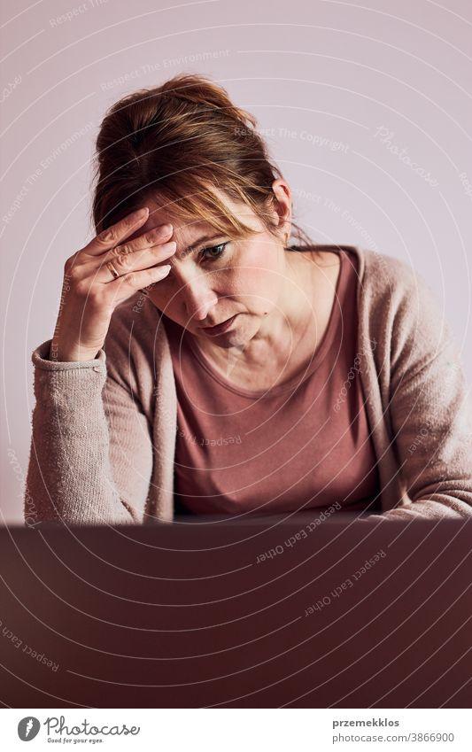 Die Frau konzentrierte sich auf ihre harte Arbeit und erledigte ihre Arbeit ferngesteuert mit einem Laptop von zu Hause aus. Frau sitzt am Schreibtisch vor dem Computer und schaut auf den Bildschirm. Konzept des Remote-Arbeitens