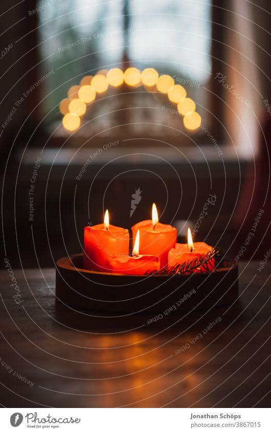 Adventskranz mit brennenden roten Kerzen auf Holztisch stehend im Wohnzimmer mit Kerzenbogen im Fenster hell Christentum Weihnachten Weihnachten & Advent