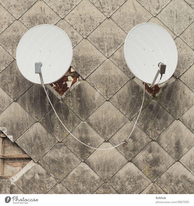 Zwei Parabolantennen en einer schmutzigen Fassade aus Asbestfaserplatten erinnern an ein Paar Ohren 2 aushorschen Fassadenplatten Asbestfaserzement Kabelsalat