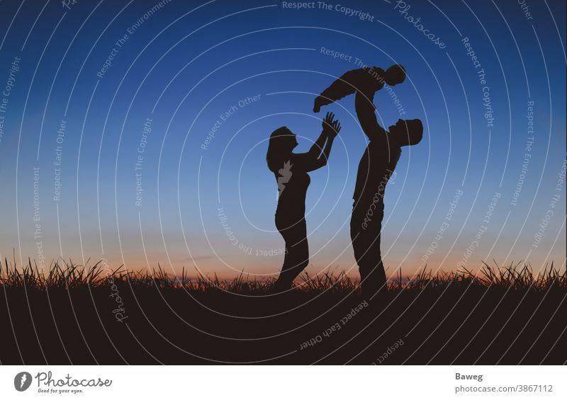 Silhouette einer Familie bei Sonnenuntergang Silhouetten Auszeit Baum Sonnenaufgang Frau Mann Kind Paar Beziehung Draussen Ehe Entspannung Freizeit Freude